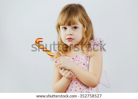 Charming little girl, with curly blond hair, wearing on pink dress and fairy wings, posing with colorful candy in her hands, on white background, in studio, waist up - stock photo