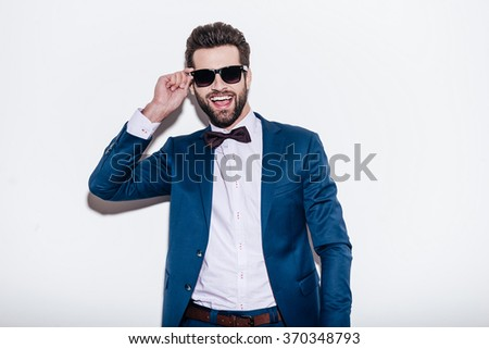 Charming macho. Handsome young cheerful man in suit adjusting his sunglasses and looking at camera with smile while standing against white background - stock photo