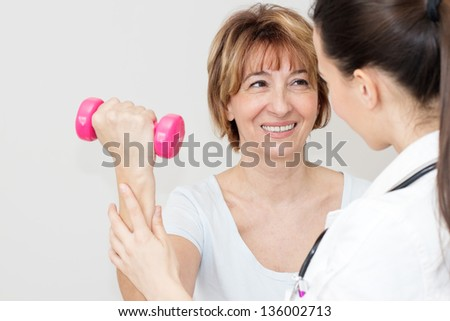 Charming  mature patient lifts dumbbells with a young physical therapist. - stock photo