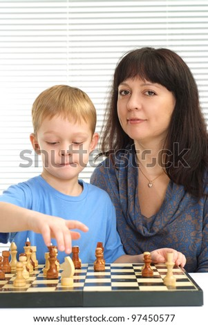 Charming mom with her son sitting playing chess on light background - stock photo