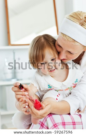 Charming mother making her little daughter's nails in the bathroom - stock photo