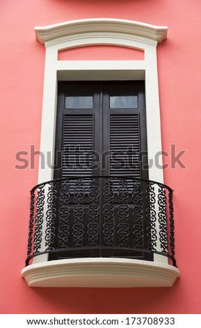 charming old Spanish balcony door on bright rose pink wall San Juan, Puerto Rico - stock photo