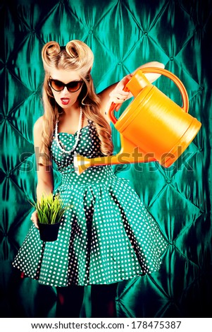 Charming pin-up woman with retro hairstyle and make-up holds watering can. - stock photo