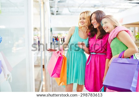 Charming shoppers discussing lingerie in the shop window - stock photo