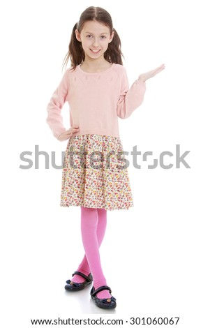Charming slim girl with long tails on their heads in a long cotton dress and a pink blouse. is pointing in the direction-Isolated on white background - stock photo