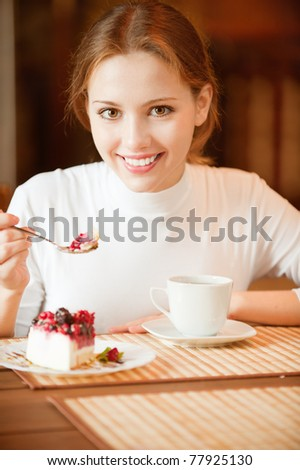 Charming smiling girl sits at table in cafe and beret spoon pie slice. Near to her there is tea cup. - stock photo