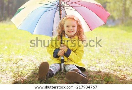 Charming smiling little girl with colorful umbrella autumn - stock photo
