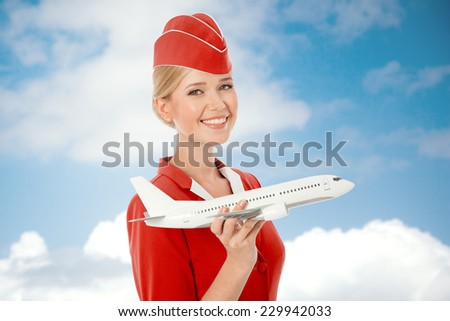 Charming Stewardess Holding Airplane In Hand. Sky With Clouds Background. - stock photo