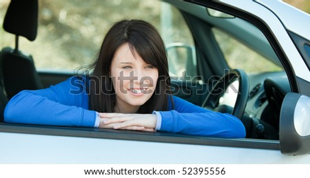 Charming teen girl smiling at the camera sitting in her car outdoor - stock photo
