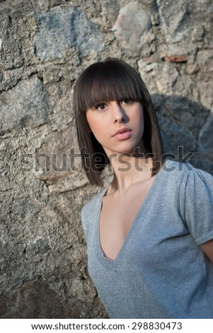 Charming teen in casual posing against a rock wall - stock photo