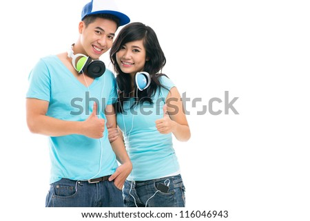 Charming teens with their thumbs up smiling at the viewer, copy-spaced - stock photo