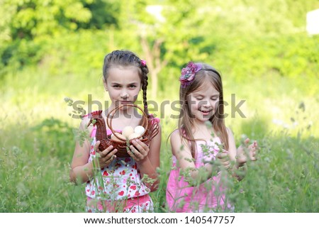 Charming two girls standing in tall green grass with basket in hand outdoors - stock photo