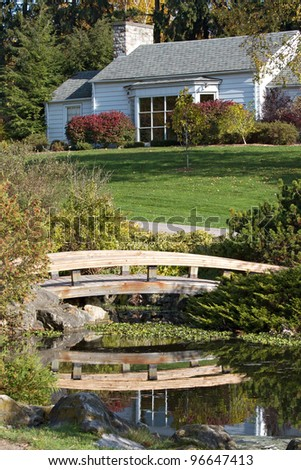 Charming white cottage and lawn viewed across pond with reflection of arched wooden footbridge. Vertical layout. - stock photo