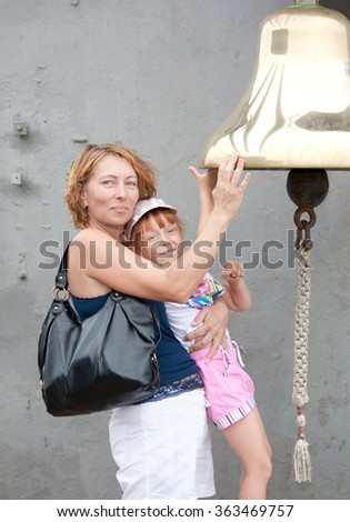 Charming woman and happy child touching the ship's bell - stock photo
