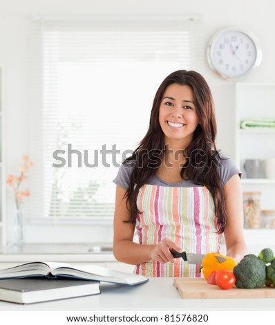 Charming woman consulting a notebook while cooking vegetables in the kitchen - stock photo