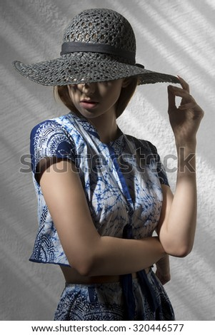 charming woman covering her eyes with cute black hat and wearing blue printed shirt and skirt. In fashion pose  - stock photo