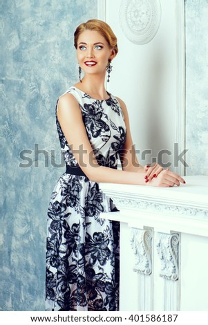 Charming woman in beautiful evening dress standing by a fireplace in a room with classical vintage interior. Jewellery. Fashion shot. Hairstyle. - stock photo
