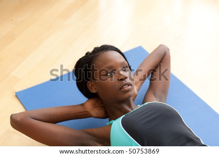 Charming woman in gym clothes doing sit-ups at home - stock photo