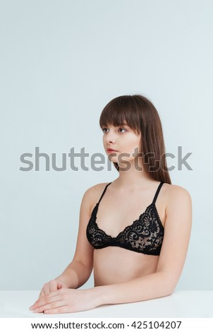Charming woman in lingerie sitting at the table and looking away isolated on a white background - stock photo