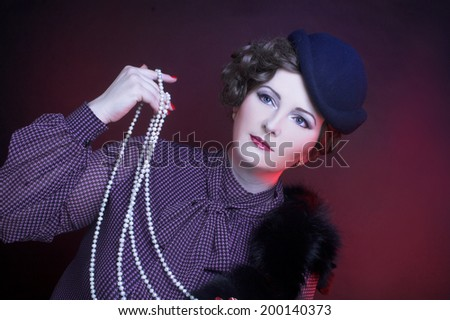 Charming woman in vintage hat posing with beads. - stock photo