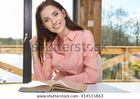 Charming woman sitting by wooden table and reading book - stock photo