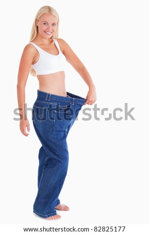 Charming woman wearing jeans that are too big - stock photo