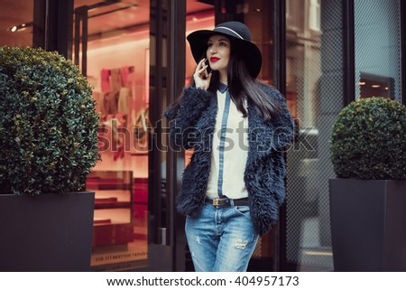 Charming woman with a beautiful smile is calling on the phone while walking to the shops, happy caucasian woman is calling his girlfriend and shows off shopping in luxury stores - stock photo