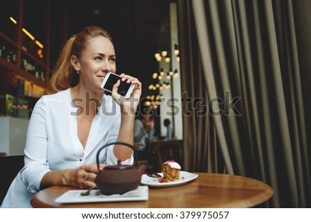 Charming woman with good mood holding mobile phone near face while relaxing in modern coffee shop interior, beautiful female dreaming about something good while waiting for a call on cell telephone  - stock photo