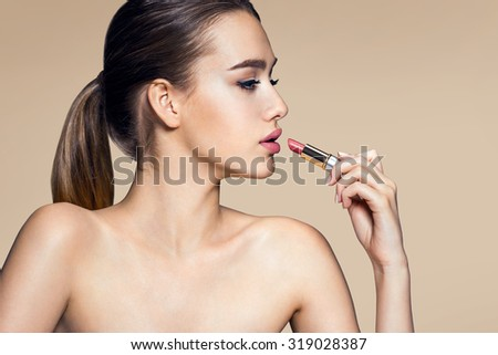 Charming young babe with lipstick / photoset of attractive brunette girl on beige background - stock photo