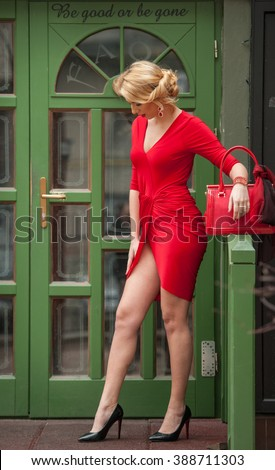 Charming young blonde in red sexy dress posing in front of a green painted door frame. Sensual gorgeous young woman on high heels in red outfit. Portrait of attractive fair hair girl with long legs - stock photo