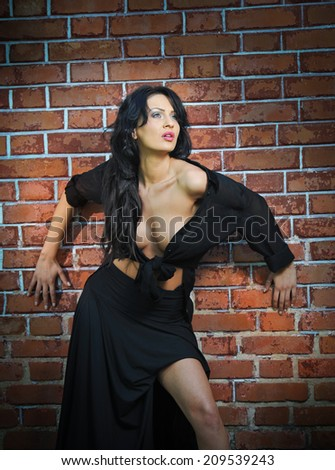 Charming young brunette woman in black near the brick wall. Sexy gorgeous young woman with low cut blouse. Portrait of a provocative woman with long hair laying against a red brick wall - stock photo