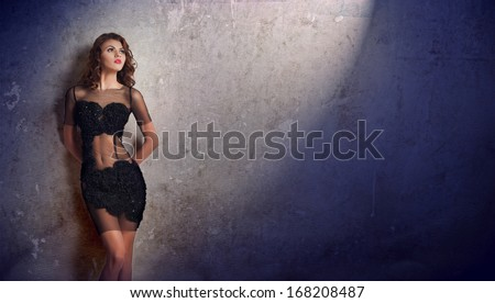 Charming young brunette woman in transparent lace black dress leaning against an old wall. Sexy gorgeous young woman near old wall. Full length portrait of a sensual woman with long hair posing - stock photo