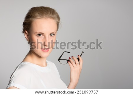 Charming young business woman holding glasses in hand - stock photo