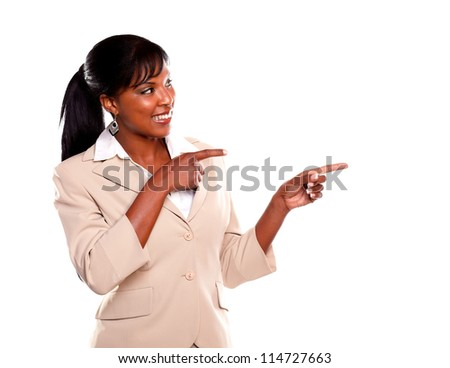 Charming young businesswoman looking and pointing left on isolated background - stock photo