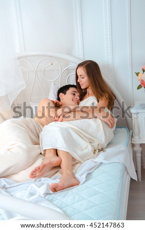 charming young couple in love lying and hugging in white bed - stock photo