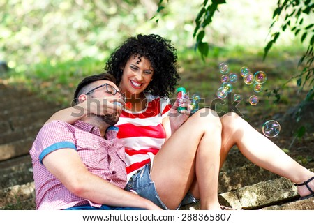 Charming young couple sitting on stairs in the park and blowing bubbles. - stock photo