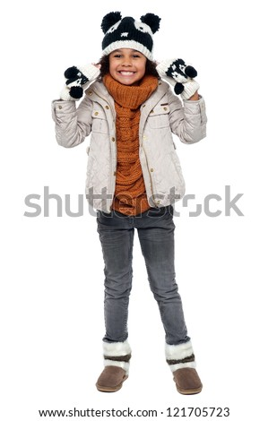 Charming young girl enjoying winters. Fully covered with warm clothing. - stock photo
