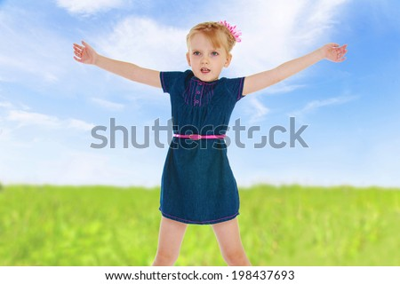 charming young girl in a blue dress enthusiastically gesturing with his hands on a background of green summer meadows. - stock photo