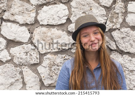Charming young girl in a straw hat on a background of a stone wall.  - stock photo