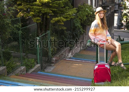 Charming young girl sitting on the railing with red suitcase. Travel to Europe. - stock photo