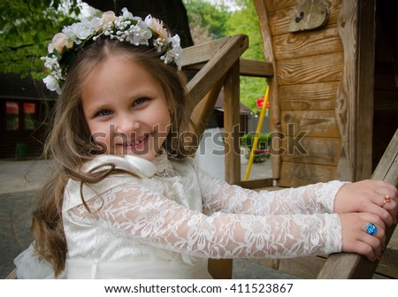 Charming young girl with long healthy hair in a beautiful white dress walking outdoors - stock photo
