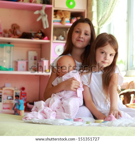 Charming young girls in the room playing with toys and having fun on the background of bright toys - stock photo