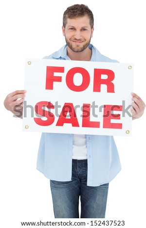 Charming young man on white background holding a for sale sign - stock photo