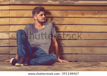 Charming young man poses outdoor in casual clothes near wooden fence as fashion concept - stock photo