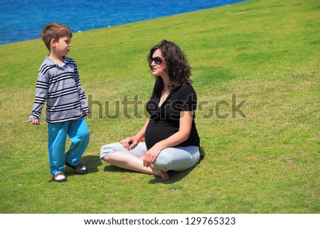 Charming young pregnant woman rests with lovely four-year-old son on the grass near the sea - stock photo