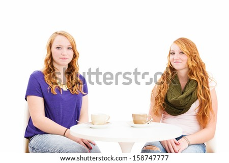 charming young redhead women sitting at a coffee table on white background - stock photo