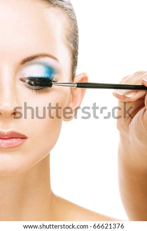 Charming young woman applying blusher eyelid close up , on red background. - stock photo