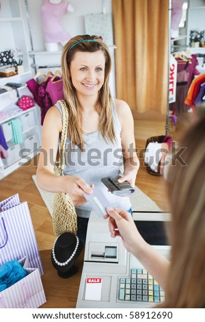 Charming young woman buying clothes with her card in a shop - stock photo