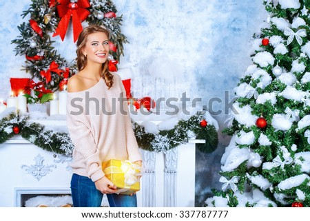 Charming young woman celebrating Christmas at home by the fireplace and a tree, beautifully decorated for Christmas. - stock photo