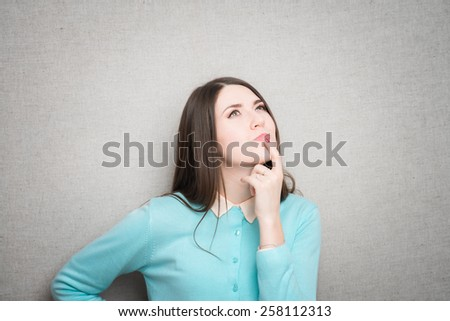 Charming young woman  has brought forefinger to mouth and looks up, reflecting on the life. - stock photo